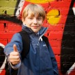 Kid standing in front of a graffiti wall - Stock Photo