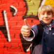 Kid standing in front of a graffiti wall - Stok fotoğraf