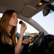 Young pretty women preparing her make-up in car - Stock Photo