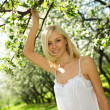 Young beautiful smiling woman in bloomin — Stock Photo