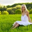 Young woman sitting on a green grass — Stock Photo #1997741