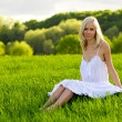 Stock Photo: Young woman sitting on a green grass