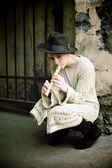 Young girl in a hat playing flute — Stock Photo