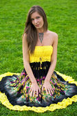 Young beautiful woman sitting on the green grass — Stock Photo