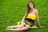 Beautiful woman sitting in green grass — Stock Photo