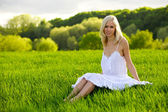 Young woman sitting on a green grass — Stock Photo