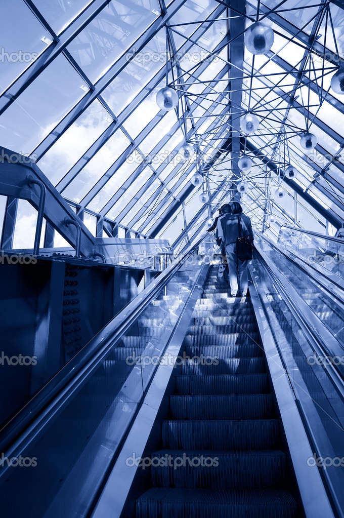 Standing on escalator in modern business center. Tint blue  Stock Photo #1998544