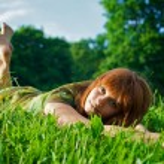 Young beautiful woman lying on grass — Stock Photo