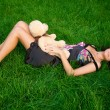 Stock Photo: Young woman lying on the green grass