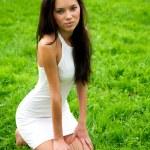 Beautiful woman sitting on the grass — Stock Photo