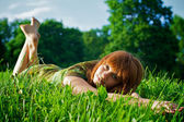 Young beautiful woman lying on grass — Stock Photo
