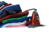Isolated steam iron and stack shirts — Stock Photo