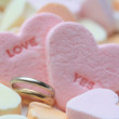 Wedding bands and candy hearts — Stock Photo