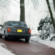 Grey limousine on a winter road — Foto Stock