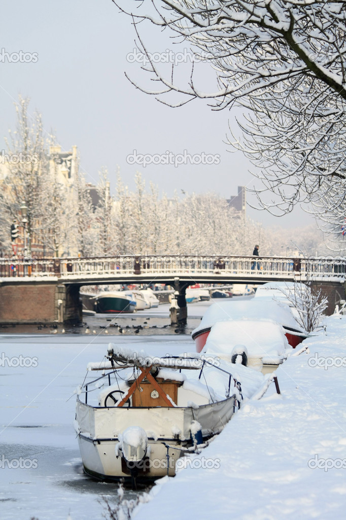 A frozen canal with snow coverd boats in Haarlem, Holland  Stock Photo #1713835