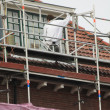 Foto Stock: Painter at work on scaffold