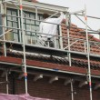 Painter at work on scaffold - Stock Photo