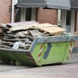 Foto Stock: Loaded dumpster near construction site