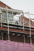 Painter at work on scaffold — Stockfoto