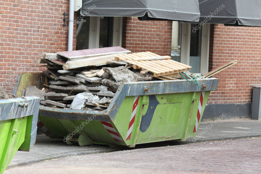 A dumpster loaded with concrete and wood near a construction site  Stock Photo #2613191