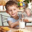 Stock Photo: Happy child pours milk from jug
