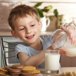 Healthy child pours milk from jug - Stock Photo