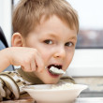 Little boy eats porridge — Stock Photo