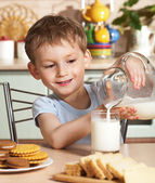 Happy child pours milk from jug — Stock Photo