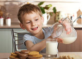 Healthy child pours milk from jug — Stock Photo
