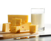 Pieces of cheese and milk glass — Stock Photo
