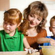 Stock Photo: Mother with children in kitchen