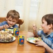 Cheerful children eat a pie — Stock Photo