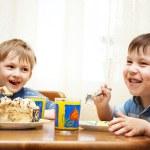 Cheerful children eat a pie — Stock Photo