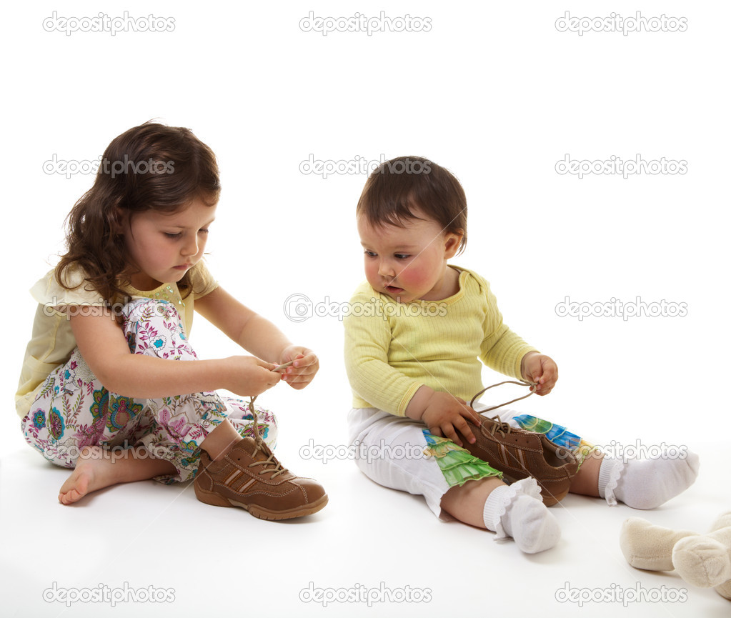 Elder sister trains younger sister to fasten laces — Stock Photo #1730102