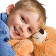Stock Photo: Little boy embraces teddy bear