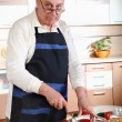Senior man cooking in kitchen — Stock Photo #2677475