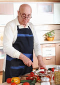 Senior man cooking in kitchen — Stock Photo