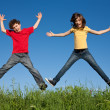 Kids jumping, running against blue sky - Stock Photo