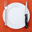 Empty plate on orange background — Stock Photo