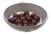 Sweet cherry in a plate on white — Stock Photo