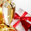 Foto Stock: Glass of champagne, gift with red tapes