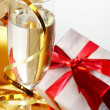Glass of champagne, gift with red tapes — Stock Photo