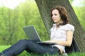 The girl with laptop on the nature — Stockfoto