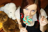 Red head girl with lollipop and teddy — Stock Photo