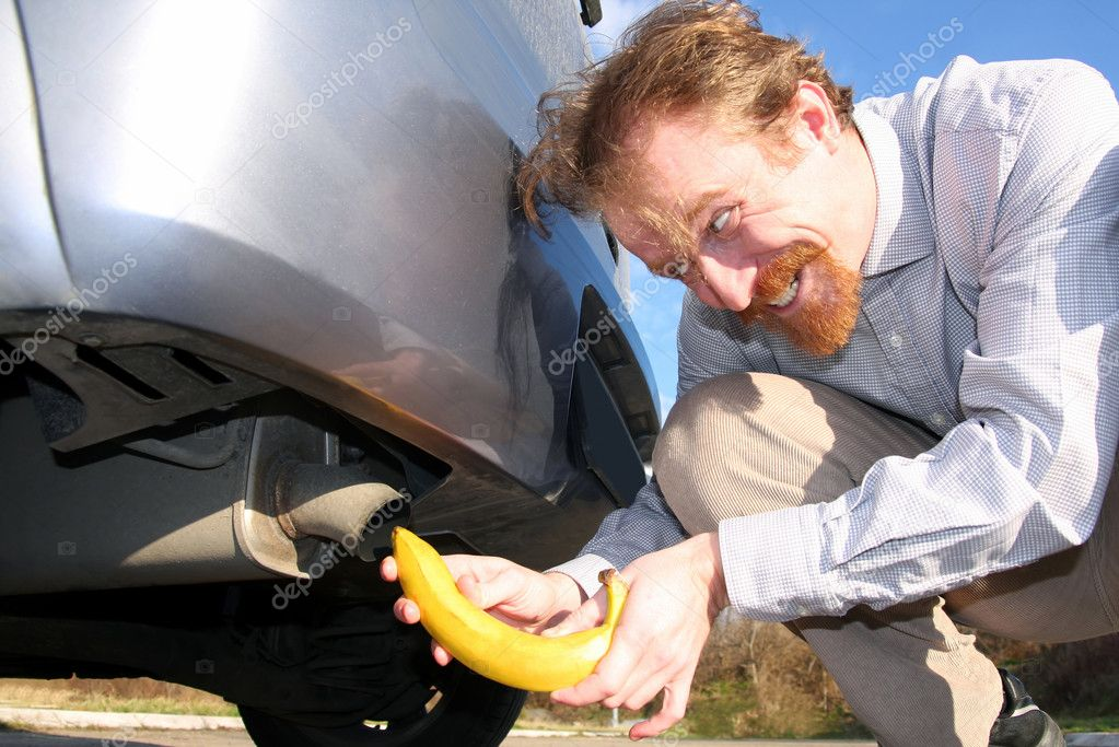 Man putting banana into car exhaust pipe — Stock Photo #1662477