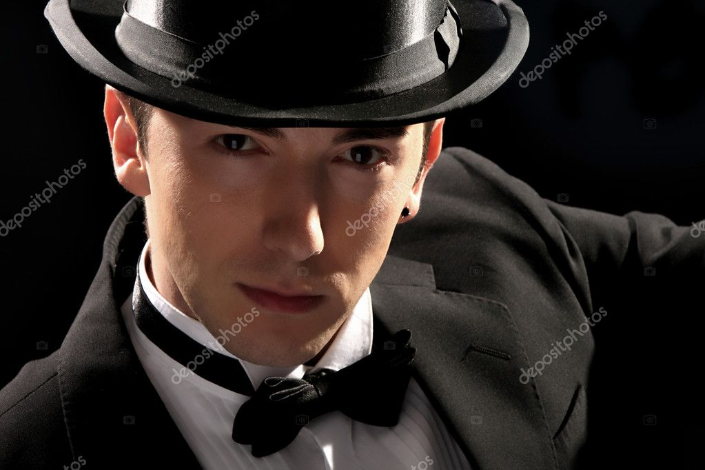 Young magician with high hat on black background — Foto Stock #1674407