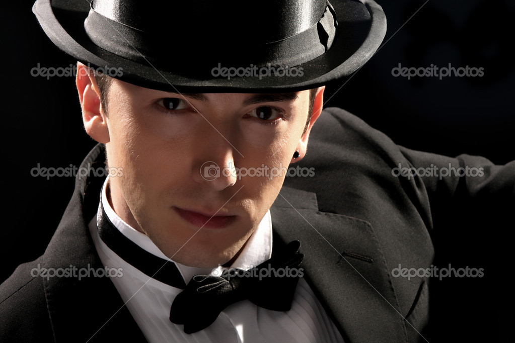 Young magician with high hat on black background — Stok fotoğraf #1674407