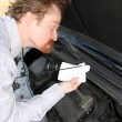 Stock Photo: Checking engine oil dipstick