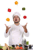 Chef juggling with peppers — Stock Photo