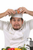 Young funny chef cracking an egg — Stock Photo